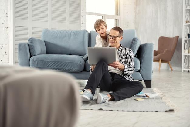 Ik koester jou. aantrekkelijke vrolijke donkerharige vader die een bril draagt en foto's op de laptop toont aan zijn zoon en zijn zoon die achter hem zit