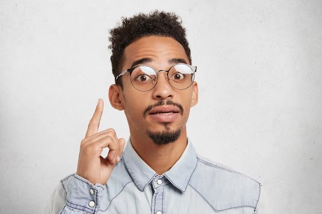 Ik krijg een geweldig idee. zelfverzekerd gemengd ras mannelijke wetenschapper draagt een jonge bril, heeft snor en baard, steekt vinger omhoog,