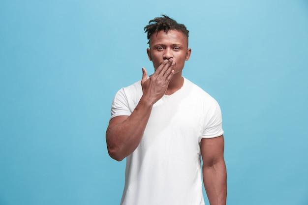 Ik kus je. portret van aantrekkelijke afromens met luchtkus op lippen. blauwe studio. mooi mannelijk portret. jonge gelukkig emotionele grappige man. menselijke gezichtsemoties concept. trendy kleuren