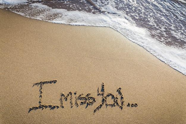 Ik mis je. liefdevol gebrek geschreven op zand
