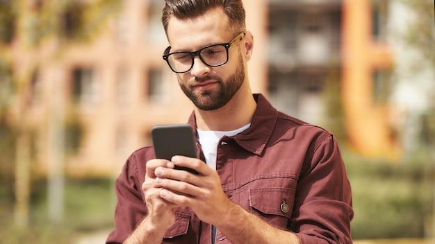 Ik moet bellen. knappe bebaarde man in vrijetijdskleding en bril die naar zijn smartphone kijkt terwijl hij op straat staat. levensstijl. digitaal. communicatie