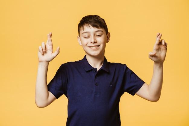 Ik moet winnen. blije jongen, steekt vingers over elkaar, doet wenselijke wens, draagt donkerpaars t-shirt, wacht op goed nieuws, staat binnen over gele muur