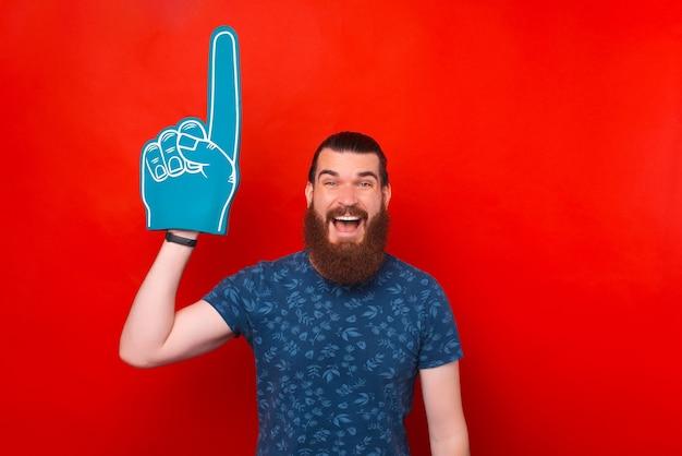 Ik nummer één fan. opgewonden bebaarde man draagt een handschoen van schuim en wijst naar boven.