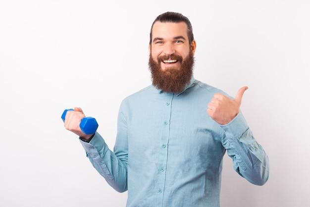 Ik raad aan om naar de sportschool te gaan. bebaarde man toont duim en houdt een halter vast.