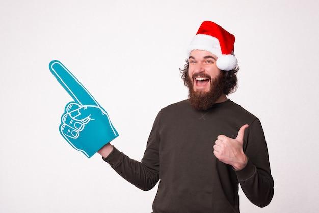 Ik raad dit echt aan, zegt een opgewonden, bebaarde man met een kerstmuts en een waaierhandschoen van schuimrubber.