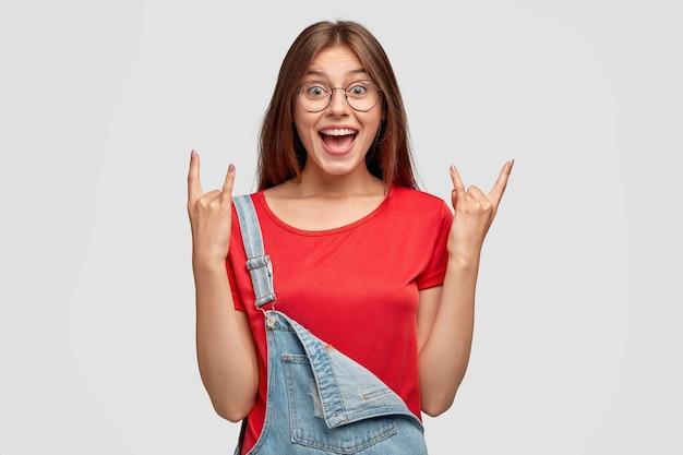 Ik regeer de wereld! glimlachende rebelse coole vrouw maakt rockgebaar, voelt zich zelfverzekerd
