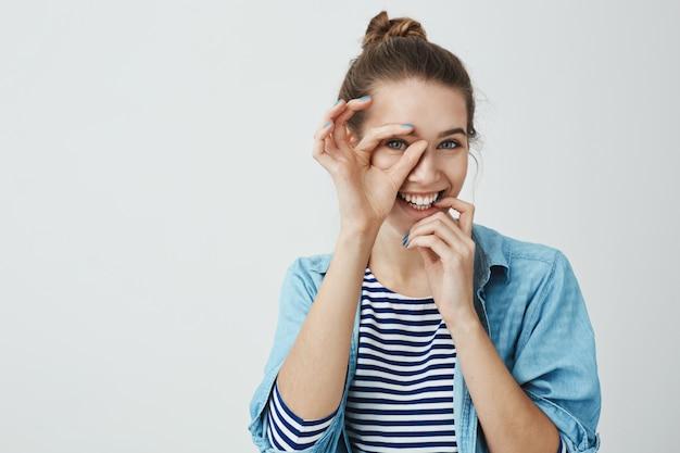 Ik richt op jou. portret van speelse gelukkig goed uitziende vriendin met knot kapsel ok teken over oog houden en op zoek dacht het, lip met de hand aanraken en breed glimlachend