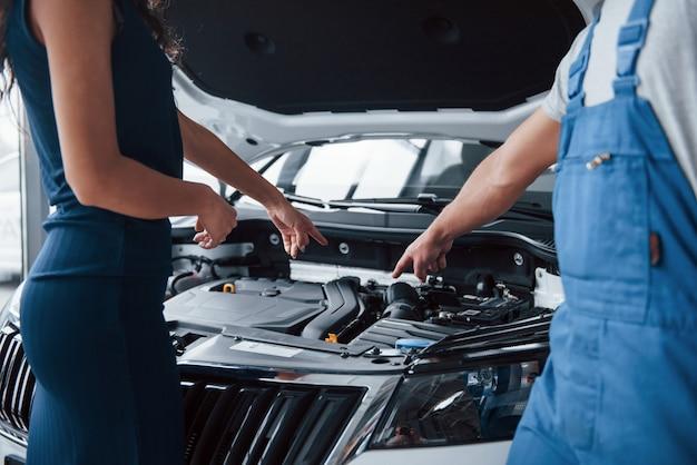 Ik vermoed uw probleem in dat deel. vrouw in de autosalon met werknemer in blauw uniform die haar gerepareerde auto terugneemt