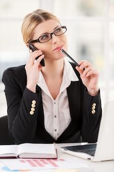 Ik vind het een goed idee. doordachte volwassen vrouw in formele kleding die op de mobiele telefoon praat en de kin aanraakt met een pen terwijl ze op haar werkplek zit