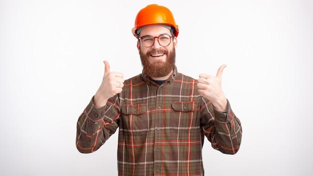 Ik vind mijn baan leuk. de gelukkige gebaarde mens maakt omhoog als gebaar of duimen met beide handen op witte ruimte.
