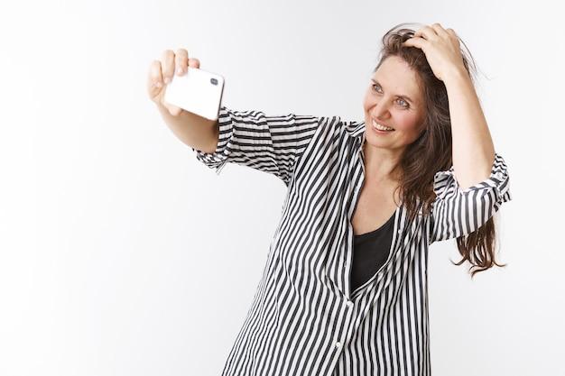 Ik voel me nog jong en mooi. portret van een charmante zelfverzekerde en energieke vrouw van middelbare leeftijd die een smartphone vasthoudt met uitgestrekte hand, een selfie neemt die het kapsel controleert en glimlacht naar de mobiele telefoon