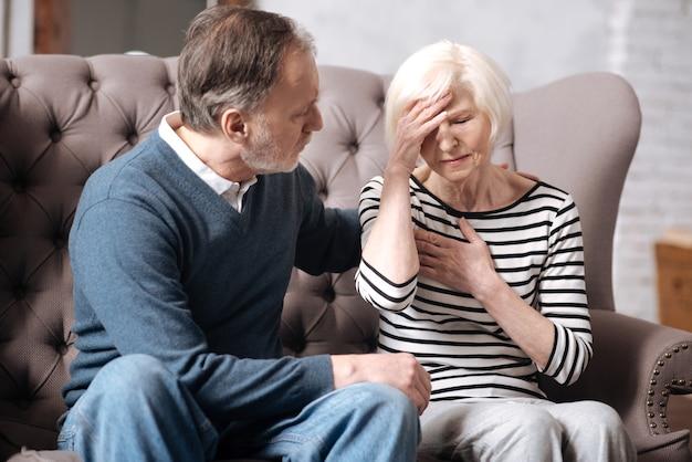 Ik voel me slecht. oudere dame raakt haar voorhoofd en hartgebied aan terwijl ze in de buurt van haar man op de bank zit.