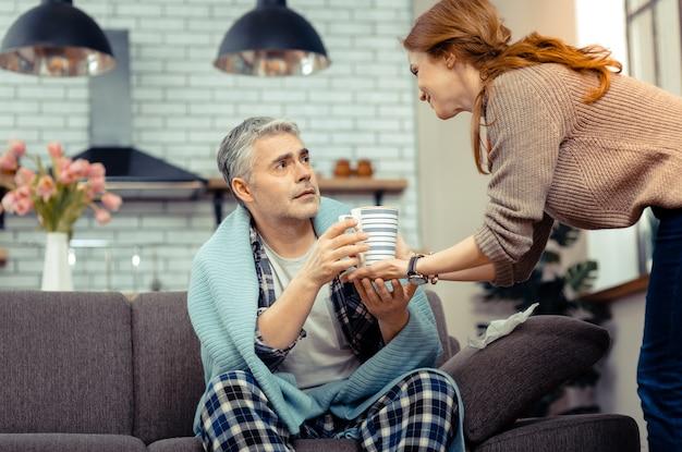 Ik voel zorg. aangename volwassen man die naar zijn vrouw kijkt terwijl hij een kopje uit haar handen neemt