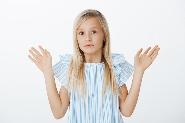 Ik was het niet, ik ben onschuldig. portret van verward nerveus klein blond meisje handpalmen opheffen in overgave en starend met geen idee van angstige uitdrukking, staande
