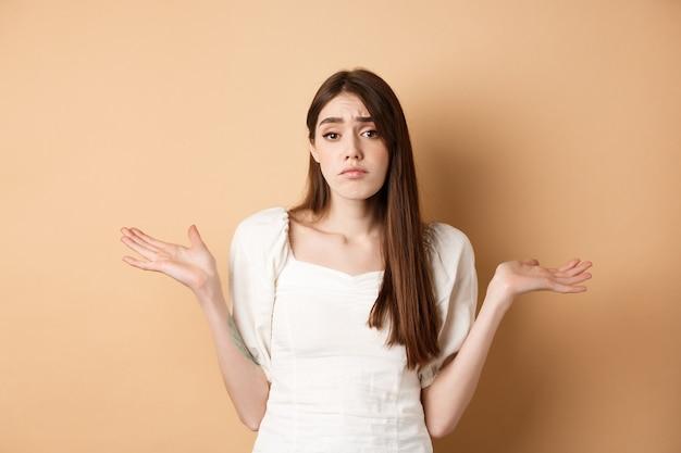 Ik weet het niet. clueless verdrietig meisje dat schouders ophaalt en onwetend kijkt, heeft niets te zeggen, staande op een beige achtergrond.