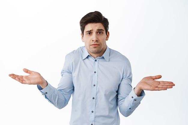 Ik weet het niet. clueless zakelijke man, kantoormedewerker die zijn schouders ophaalt en verward kijkt, verbaasd tegen de witte muur