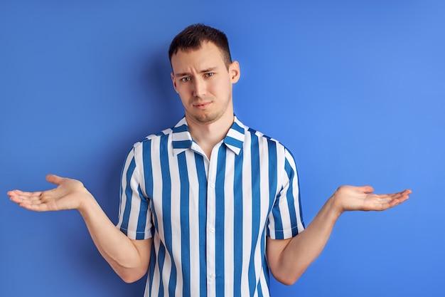 Ik weet het niet. man misverstand, schouderophalend en camera kijken, verwarde uitdrukking op het gezicht, geïsoleerde blauwe achtergrond