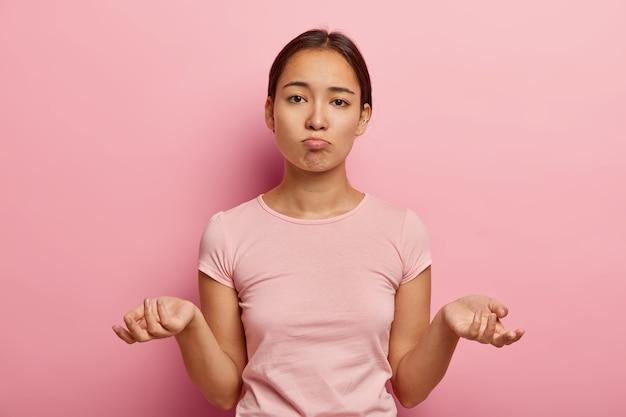 Ik weet het niet. onbewust perplex jonge aziatische vrouw spreidt handpalmen zijwaarts, heeft geen idee wat ze moet doen, gekleed in een casual t-shirt, kijkt droevig, denkt na over hoe te handelen in een lastige situatie