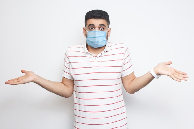 Ik weet het niet. portret van een verwarde jongeman met een chirurgisch medisch masker in een gestreept t-shirt met opgeheven armen en weet niet wat te doen. indoor studio opname, geïsoleerd op een witte achtergrond.