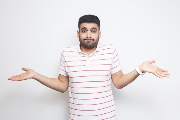Ik weet het niet. portret van een verwarde knappe bebaarde jongeman in een gestreept t-shirt die met opgeheven armen staat en niet weet wat hij moet doen. indoor studio opname, geïsoleerd op een witte achtergrond.