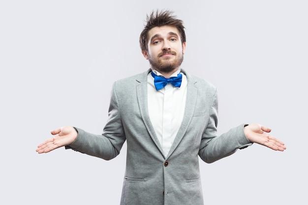 Ik weet het niet. portret van een verwarde knappe bebaarde man in een casual grijs pak en een blauwe vlinderdas die met opgeheven armen staat en naar de camera kijkt. indoor studio opname, geïsoleerd op lichtgrijze achtergrond.