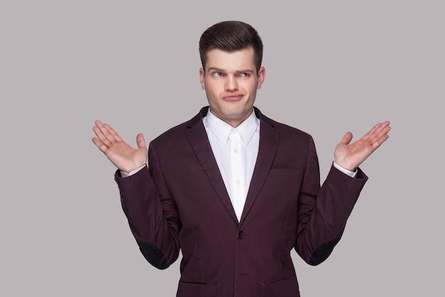 Ik weet het niet. portret van een verwarde knappe jongeman in violet pak en wit overhemd, staand, wegkijkend, opgeheven armen en denkend. indoor studio opname, geïsoleerd op een grijze achtergrond.