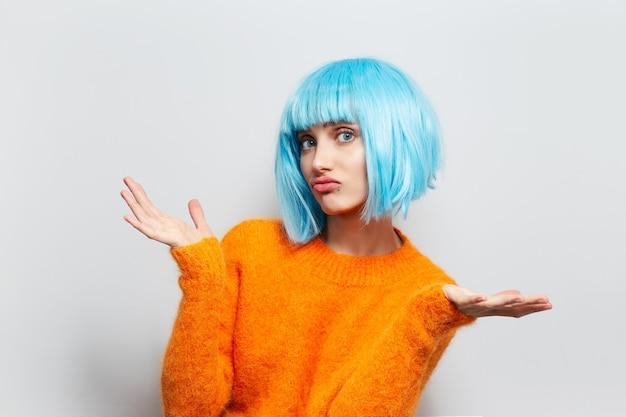 Ik weet het niet. portret van leuk meisje met blauw haar in oranje sweater op witte muur.