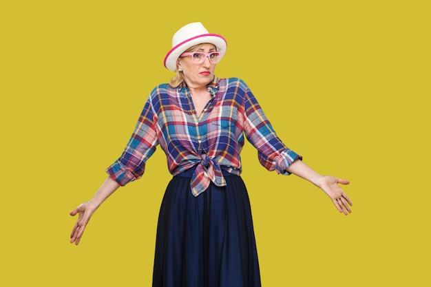 Ik weet het niet. portret van verwarde moderne stijlvolle volwassen vrouw in casual stijl met hoed en bril staan, denken, opgeheven armen, wegkijkend. indoor studio opname geïsoleerd op gele achtergrond.
