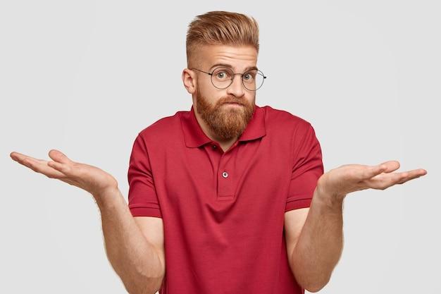 Ik weet niets. knappe stijlvolle hipster met dikke gemberbaard, spreidt zijn handpalmen met een vragende uitdrukking