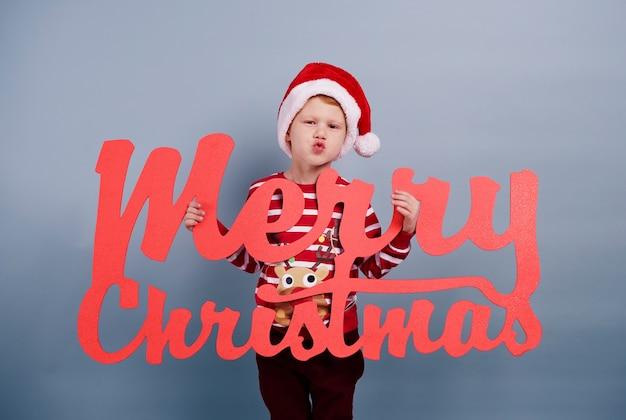 Ik wens jou een prettig kerstfeest. jongen met vrolijk kerstfeest belettering
