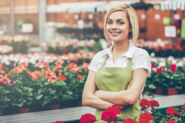 Ik werk graag met bloemen. mooie jonge vrouw in schort die haar armen gekruist houdt en glimlacht terwijl ze in een kas staat met bloemen om haar heen