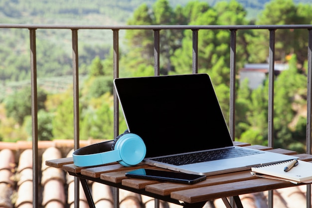 Ik werk vanaf het terras van het huis, tafel op het terras met draagbare koptelefoons en notitieblok.