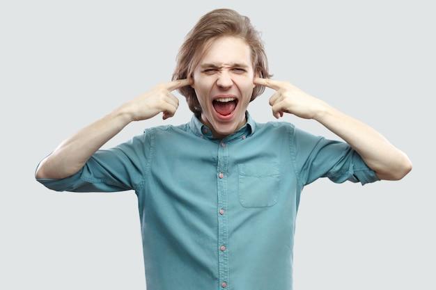 Ik wil dit niet horen. portret van een boze, knappe, langharige blonde jongeman in een blauw shirt die staat, vingers in de oren steekt en schreeuwt. indoor studio opname, geïsoleerd op lichtgrijze achtergrond.
