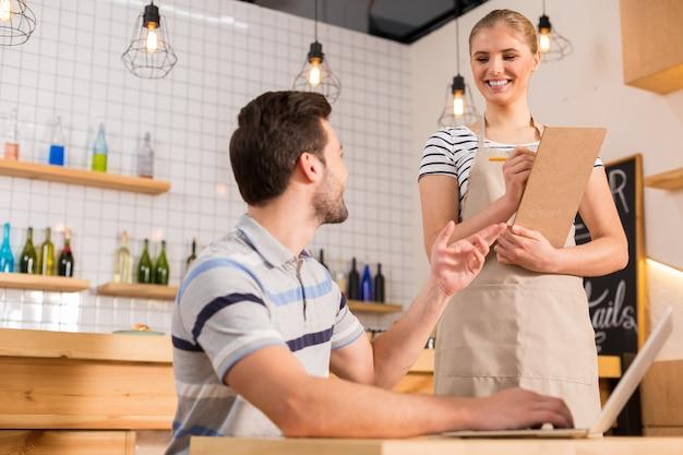 Ik wil eten. vrolijke aardige hongerige man die naar de serveerster kijkt en een bestelling plaatst terwijl hij in het café is