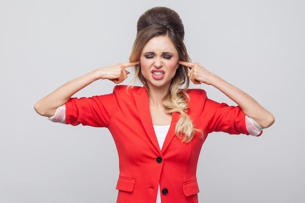 Ik wil het niet horen. nerveuze zakenvrouw met kapsel en make-up in rode mooie blazer, staande tanden op elkaar klemmend en vinger in de oren. indoor studio opname, geïsoleerd op een grijze achtergrond.