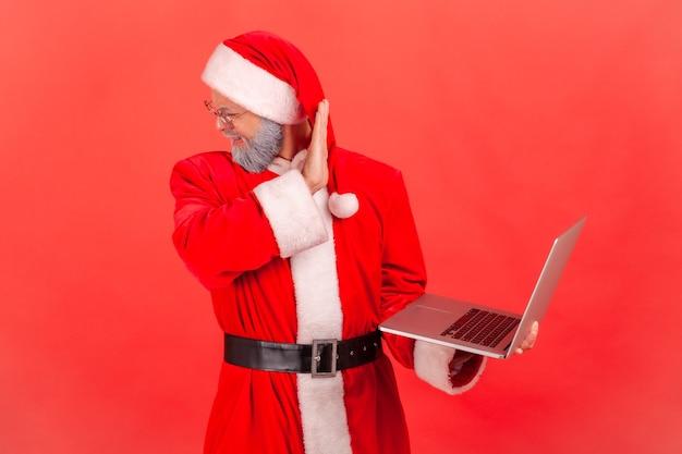 Ik wil hier niet naar kijken. de kerstman wendt zijn gezicht af van de computer, geschokte inhoud.