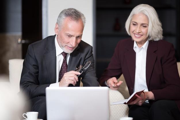 Ik wil je iets laten zien. opgetogen betrokken bejaarde zakenman lachend en zittend op kantoor voor de laptop terwijl hij met zijn collega werkte en ideeën uitwisselde