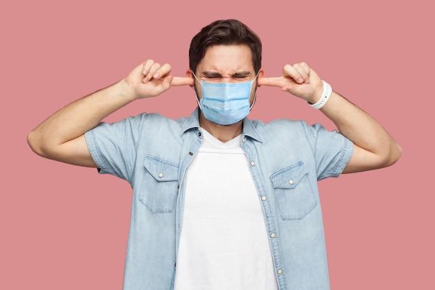 Ik wil je niet horen. portret van een verwarde jongeman met een chirurgisch medisch masker in een blauw shirt dat staat en vingers op de oren legt en het kan hem niet schelen. indoor studio-opname, geïsoleerd op roze achtergrond