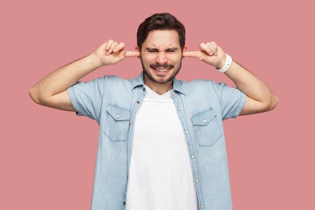 Ik wil je niet horen. portret van een verwarde knappe bebaarde jongeman in een blauw casual stijlshirt dat staat en vingers op de oren legt en het kan hem niet schelen. indoor studio-opname, geïsoleerd op roze achtergrond