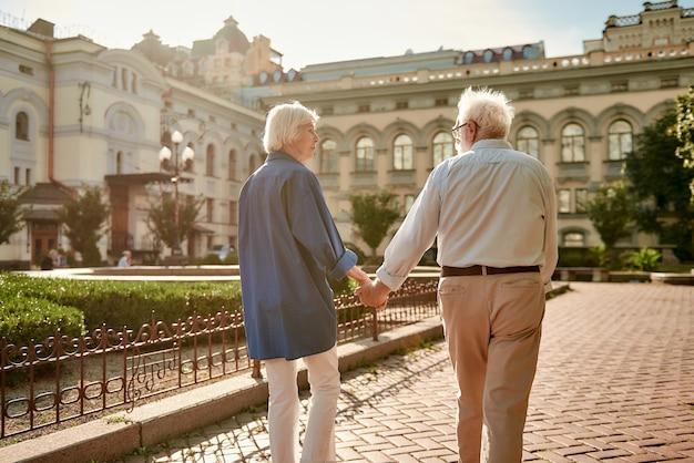 Ik wil met je meereizen achteraanzicht van een ouder echtpaar dat elkaars hand vasthoudt terwijl ze samen buiten wandelen