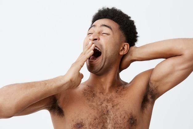 Ik wil slapen. sluit omhoog portret van knappe atletische jonge afro amerikaanse kerel met krullend haar en de naakte kleding van de torsokleding terwijl geeuw, die na lange dag op het werk naar bed gaan.