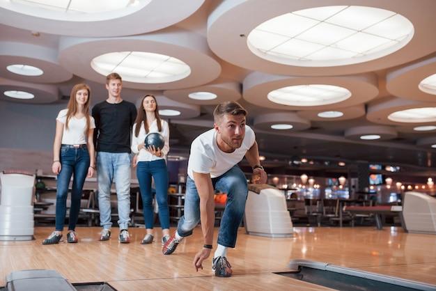 Ik wil toeslaan. jonge, vrolijke vrienden vermaken zich in het weekend in de bowlingclub