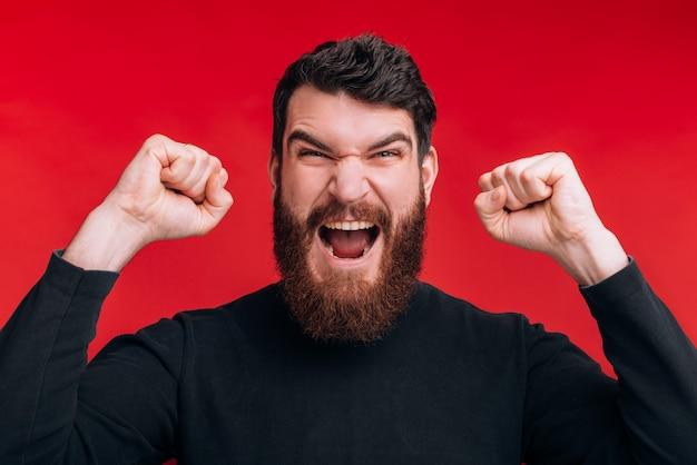 Ik wist het, ik heb gewonnen close-up portret van een sterk schreeuwende bebaarde man die het winnaargebaar op de rode muur maakt.