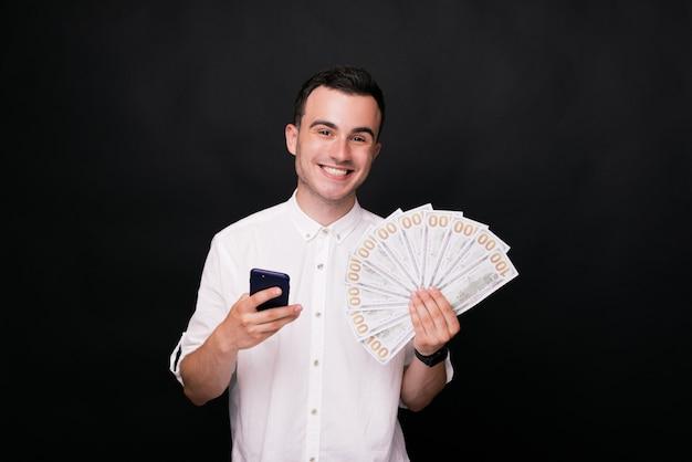Ik won! de jonge glimlachende mens bij de camera, die zijn telefoon houdt is de andere hand op zwarte achtergrond in wit overhemd.