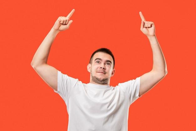 Ik won. winnend succes gelukkig man vieren een winnaar te zijn. dynamisch beeld van kaukasisch mannelijk model op oranje studioachtergrond