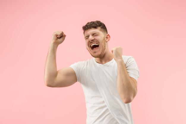 Ik won. winnend succes gelukkig man vieren een winnaar te zijn. dynamisch beeld van kaukasisch mannelijk model op roze studioachtergrond.