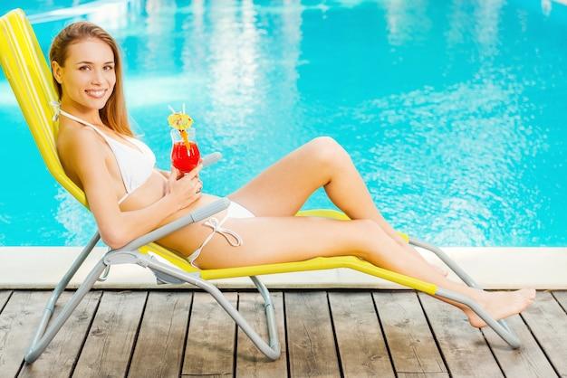 Ik wou dat dit moment voor altijd kon duren. zijaanzicht van mooie jonge vrouw in witte bikini cocktail drinken en glimlachen terwijl u ontspant in de ligstoel bij het zwembad