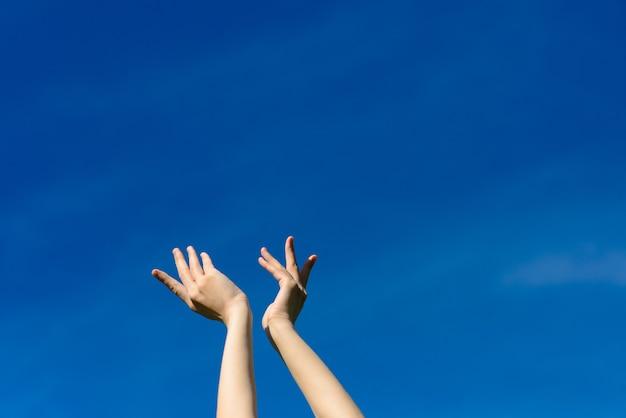 Ik wou dat we de lucht konden aanraken, vrouwelijke handen uitstrekkend naar de blauwe lucht. vrijheid en lente concept