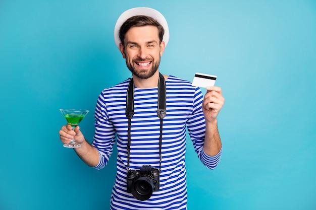 Ik zal betalen! foto van aantrekkelijke kerel fotograaf houden digitale camera reiziger kopen creditcard groen cocktail slijtage gestreepte matroos shirt vest cap geïsoleerde blauwe kleur