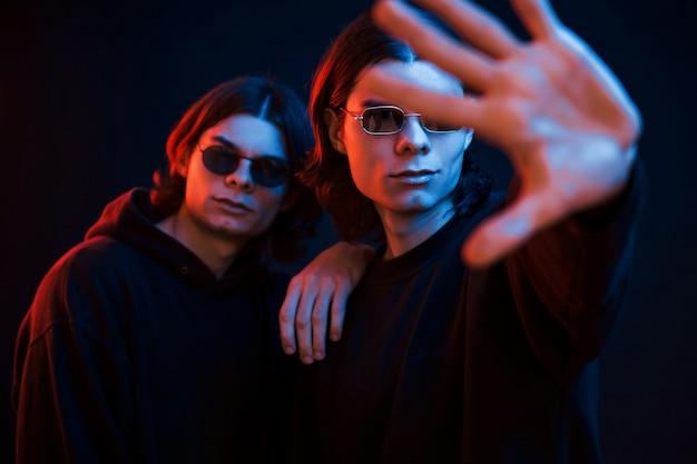 Ik zal je beschermen. portret van tweelingbroers. studio opname in donkere studio met neonlicht